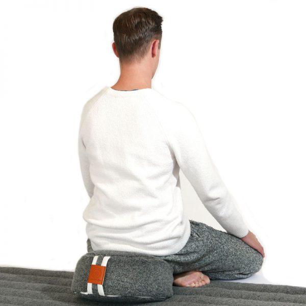 lotus houding op een wollen antraciet meditatie kussen en yogamat