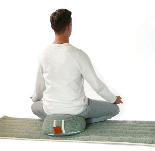 lotus houding op een wollen groen meditatie kussen en yogamat