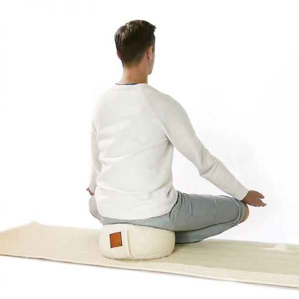 lotus houding op een wollen naturel meditatie kussen en yogamat